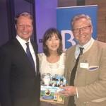 Moderatorin Sabine Sauer freut sich über Tragerl KMK