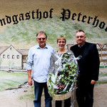Peter Neidl, Kaufmännischer Leiter der Schlossbrauerei Naabeck (rechts), gratuliert den Wirtsleuten vom Peterhof mit einem Blumengeschenk für den Wechsel zur Schlossbrauerei Naabeck. Bild: L. Ehras