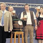 """Nach zwei Schlägen verkündet Oberbürgermeister Andreas Feller (Vierter von links): """"O zapft is'"""". Auf der Bühne stoßen unter anderem Landrat Thomas Ebeling (rechts), die Bürgermeisterinnen Ulrike Roidl (Zweite von rechts) und Martina Englhardt-Kopf (Vierte von rechts) sowie Brauerbesitzer Wolfgang Rasel (Dritter von links) mit den Besuchern im voll besetzen Zelt auf das Gelingen des Volksfestes an."""